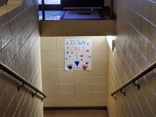 School stairwell with a sign that points down, indicating one way traffic
