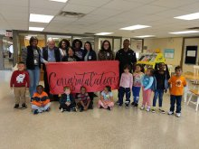 School & District Staff along with students holding up a congratulations banner at at Ridgecrest Elementary