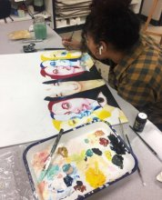 A student painting faces in various colors