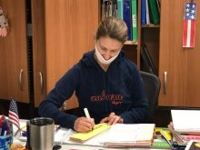 Teaching at Desk Writing on Yellow Paper