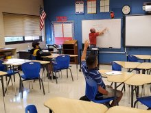 Socially-distanced student raising their hand while teacher explains a math problem