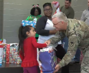 Brigadier General Pardew handing a present to a little girl