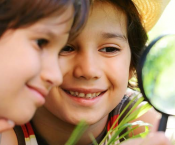 Two students looking through a magnifying glass