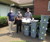 Two Toyota AL employees with Warren Jackson, holding up a bin full of face masks and standing with several other bins