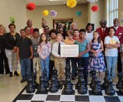 MLK Students, Staff, Fraternity Visitors, Michelle Watkins pose behind giant chess set