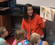 Ms. Melissa Turner reading a book with students in the library