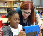 Ms. Beth Locy helping a student with their iPad
