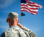 United States Flag billowing in front of a saluting soldier