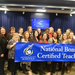 All teachers receiving national board certification recognized in December 2019, holding a NBCT banner alongside Superintendent Finley