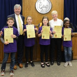 Destination Imagination Team from Blossomwood receiving board resolution from Dr. Akin.