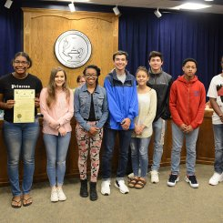 Lee High Media Arts Program Students receiving board resolution from Dr. Akin.