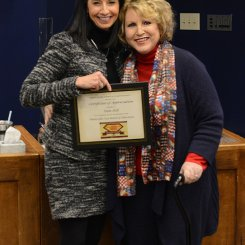 Ms. Pam Hill receiving a board resolution from Superintendent Finley for Board Appreciation Week
