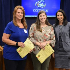 Jo Stafford and Jessica Hipp receiving a board resolution from Superintendent Finley